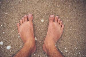 Young man's feet on the beach photo