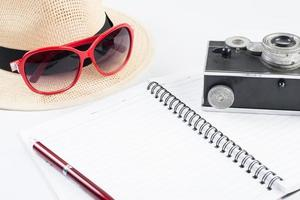 Hat, sunglasses and vintage camera with notepad isolated on a white background photo