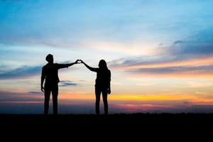 Silhouette of young couple together during sunset photo
