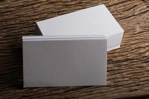 Blank white business card on wood background photo