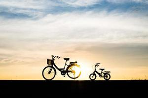 Two vintage silhouette bicycles at sunset photo