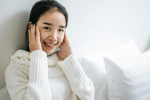 Young woman sitting on her bed with hands touching cheeks photo