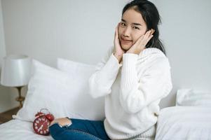 Mujer joven sentada en su cama sonriendo felizmente foto