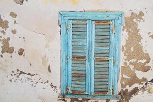 Ventana de persiana de madera azul en una pared con pintura gris desconchada