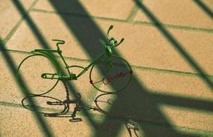 Green miniature wire bicycle with shadows on concrete pavement