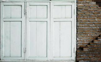 White shutters on brick wall photo