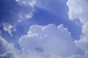 Sunlight through white clouds in blue sky photo