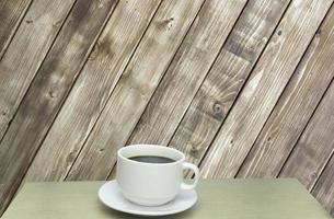 taza de café contra la pared de madera foto