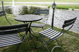 Outdoor table and chairs near water photo
