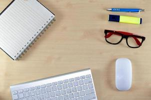 Desktop view with keyboard, notebook, and glasses