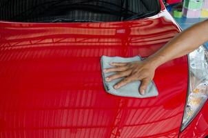 persona limpiando un auto rojo foto