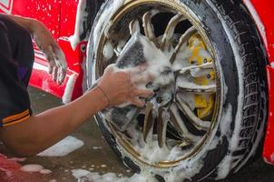Washing the tires of a red car photo