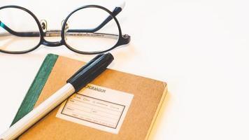 cuaderno con bolígrafo y anteojos foto