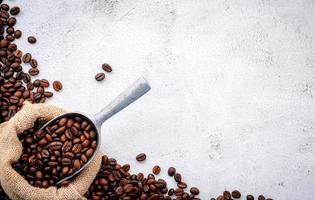 Roasted coffee beans with scoops setup on white concrete background