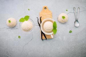 Vanilla ice cream flavor in bowl with vanilla pods on concrete background photo