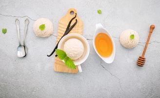 Vanilla ice cream flavor in bowl with vanilla pods and honey