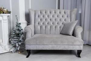Sofá de terciopelo gris con un pequeño árbol de navidad en la sala de estar
