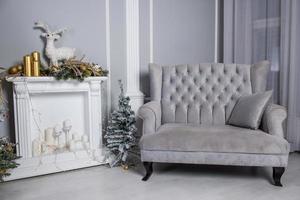 Velvet gray sofa with small Christmas tree, false fireplace, and Christmas decorations photo