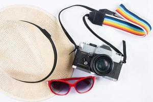 Hat, sunglasses and vintage camera isolated on a white background photo