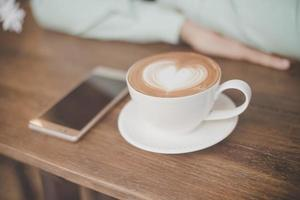 Man's hand with cup of latte art coffee and smartphone at cafe bar photo