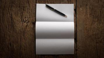 White blank folded paper on wooden table photo