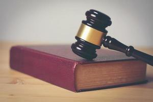 Close-up de un martillo de juez sobre un fondo de madera foto