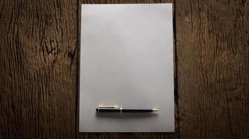 Hoja de papel en blanco y lápiz sobre una mesa de madera foto
