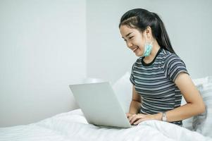 A young woman playing on her laptop in bed