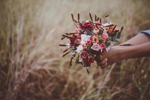 Hands holding a bouquet of red roses on summer holiday photo