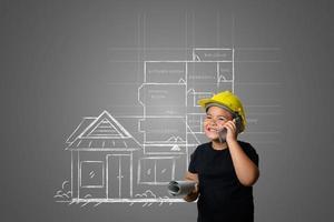Joven con un sombrero de ingeniero amarillo e ideas del plan de la casa en una pizarra
