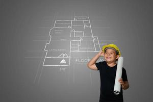 un niño con un sombrero de ingeniero amarillo y un plano de la casa en la pizarra