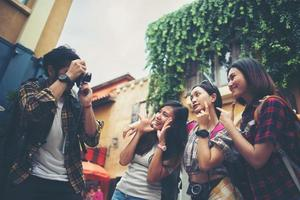 Group of happy friends taking selfies together in an urban area