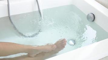 as pernas da senhora relaxam deitada na banheira branca com água