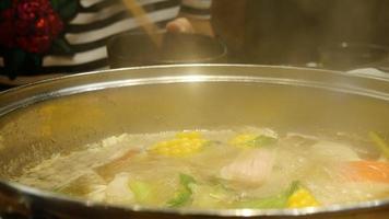 pessoas comendo sukiyaki em uma panela fervendo