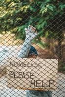 mendigos en una valla con mensajes para personas sin hogar por favor ayuden
