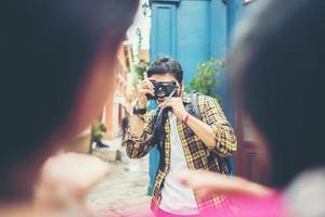joven tomando fotos de sus amigos mientras viajaban juntos en una zona urbana