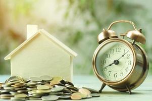 monedas con un reloj despertador y una casa modelo foto