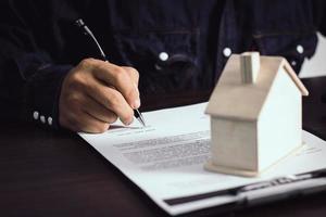 persona escribiendo en un contrato foto