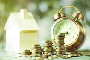 un montón de monedas con una casa modelo y un reloj despertador