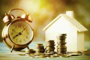 pila de monedas con una casa modelo y reloj despertador foto