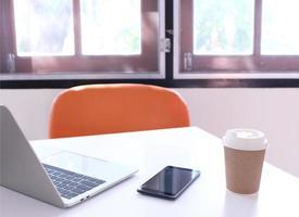 escritorio con una computadora portátil, teléfono y café en él