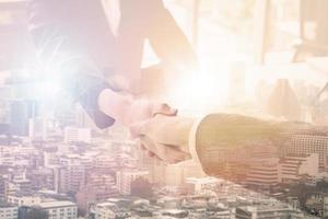 Two people shaking hands with city background photo