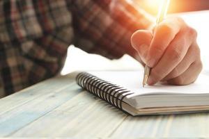 persona escribiendo en un diario foto