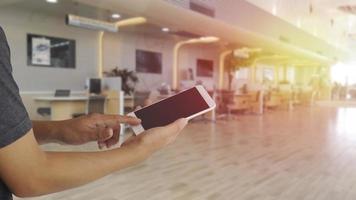 Manos con teléfono inteligente móvil de pantalla en blanco con fondo borroso en la oficina foto