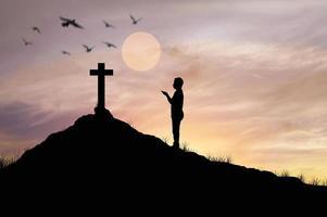 silueta, hombre, rezando, delante de, cruz foto