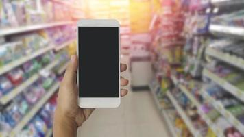 Manos con teléfono inteligente móvil de pantalla en blanco con fondo borroso en grandes almacenes