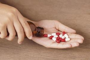Woman pouring capsules in hand photo