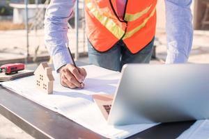 Ingeniero cepillando y trabajando en la mesa en el sitio de trabajo de construcción foto