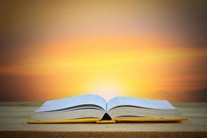 Open book with sunset background
