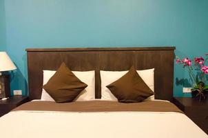 Pillows on a brown bed in a blue room